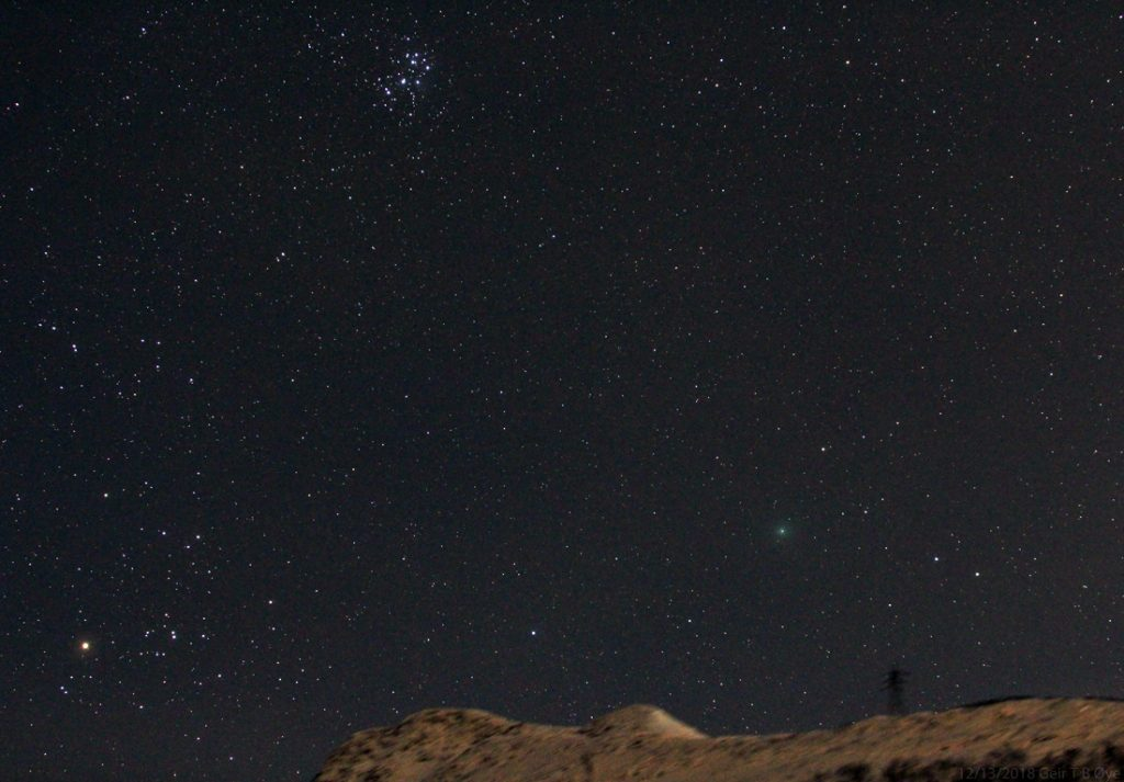 Comet 46P/Wirtanen rising above the mountain ridge. The Hyades to the left, and The Pleaiades above. Sigma 50-500mm lens, Canon 700D, ISO: 3200, Exp: 39 seconds.