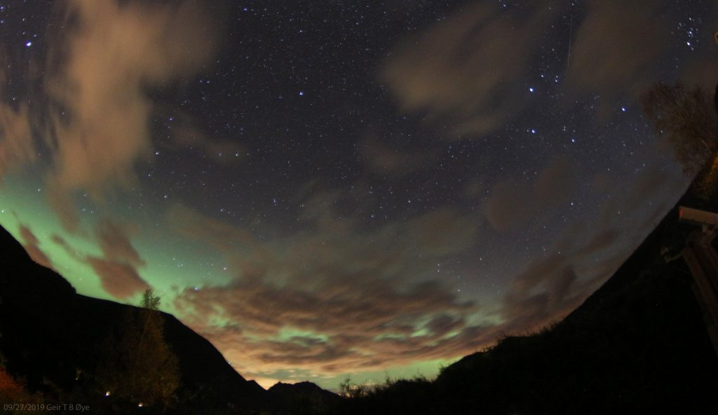 A skyscape with clouds and greenish aurora seen over Ørsta, Norway.